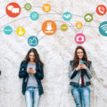 Social network concept with smiling young people holding smart phones in front of big white wall.